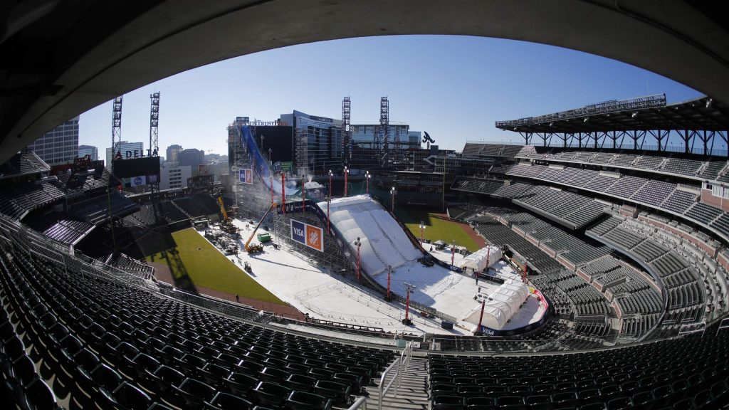 Crews work to construct and cover a giant ski slope with snow on the playing field at SunTrust Park Wednesday, Dec. 18, 2019, in Atlanta. The baseball stadium, home of the Atlanta Braves, will host the Big Air ski and snowboard competition Friday and Saturday. (AP Photo/John Bazemore)