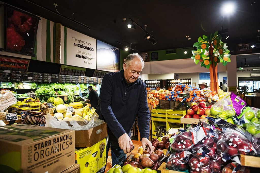 Tom Clark Sr. stacks pears inside of Clark's Market 10 days before his retirement.
