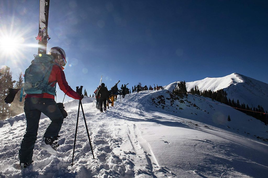 Eryn Barker, left, follows the line hiking up to the Highland Bowl gate on opening day at Aspen Highlands on Saturday, December 7, 2019. (Kelsey Brunner/The Aspen Times)
