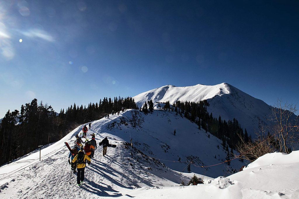 People hike up to the main gate of Highland Bowl during opening day at Aspen Highlands on Saturday, December 7, 2019. (Kelsey Brunner/The Aspen Times)
