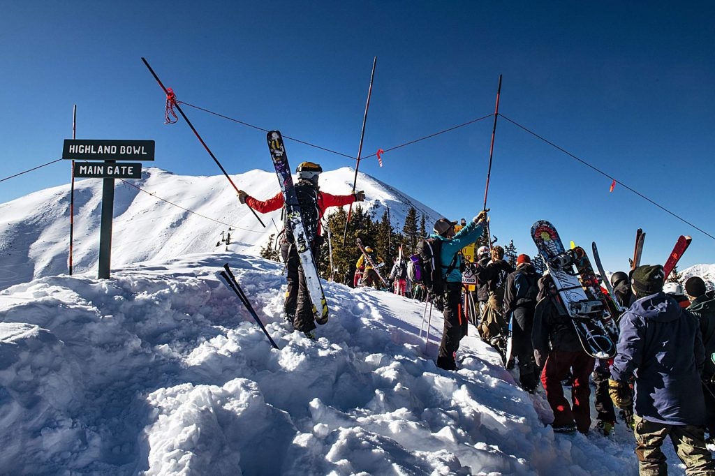 Skiers file through as the rope is lifted on the main gate of Highland Bowl during opening day on Saturday, December 7, 2019. (Kelsey Brunner/The Aspen Times)
