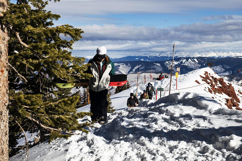 People hike up the ridge leading to Highland Bowl during opening day at Aspen Highlands on Saturday, December 7, 2019. (Kelsey Brunner/The Aspen Times)