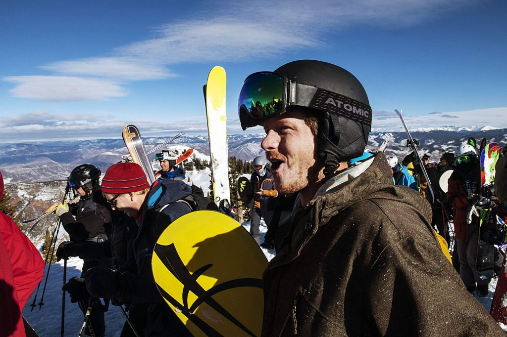 Skiers and snowboarders cheer excitedly as the rope is lifted and the hike up Highland Bowl continues during opening day on Saturday, December 7, 2019. (Kelsey Brunner/The Aspen Times)