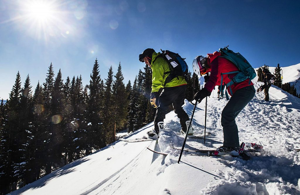 Eric Fisher, left, and Eryn Barker prepare to drop into a line off of the Highland Bowl hike during opening day at Aspen Highlands on Saturday, December 7, 2019. (Kelsey Brunner/The Aspen Times)