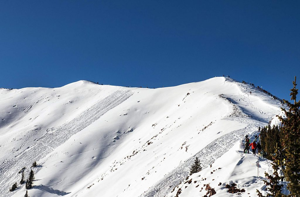 People hike along the outer ridge for Highland Bowl during opening day at Aspen Highlands on Saturday, December 7, 2019. (Kelsey Brunner/The Aspen Times)