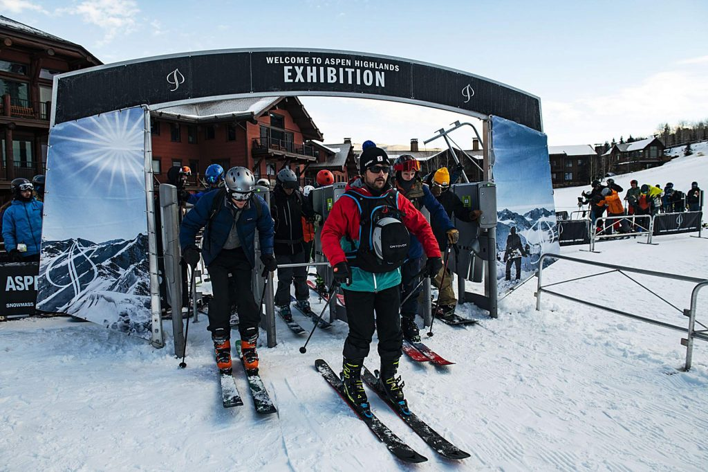 Skiers come through the turnstile of the Exhibition Lift on opening day at Aspen Highlands on Saturday, December 7, 2019. (Kelsey Brunner/The Aspen Times)