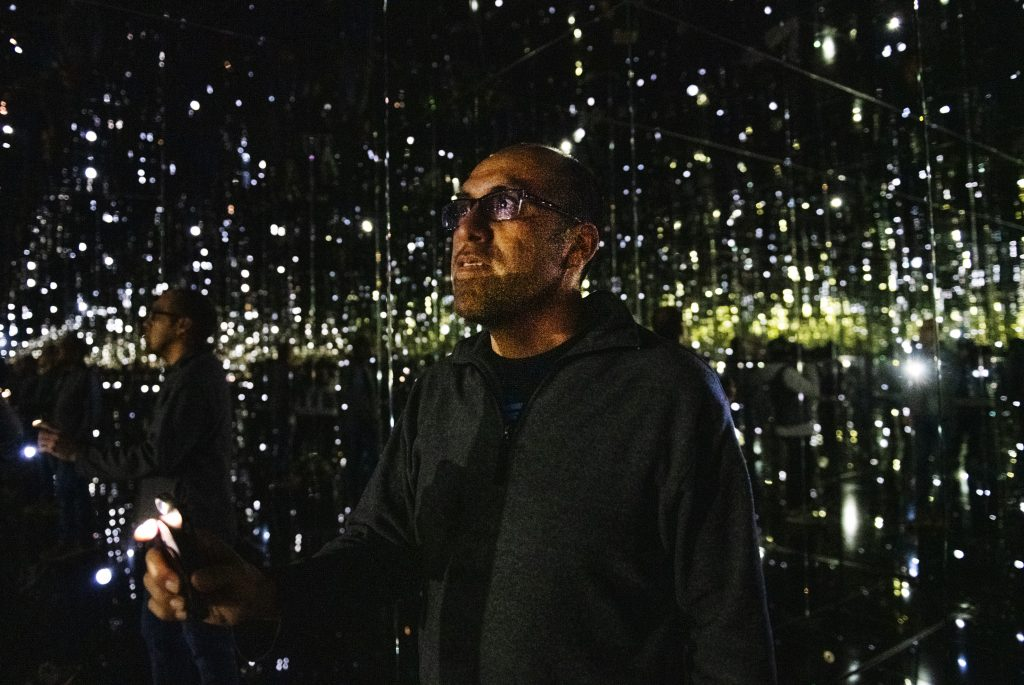Chief Operating Officer for Aspen Art Museum Luis Yllanes uses his cell phone to add more lights to Yayoi Kusama's new exhibition, Where the Lights in My Heart Go, during a sneak peek on Wednesday, December 18, 2019. The infinity room exhibition officially opens on December 20 and will be available, free to the public, until May 10, 2020.