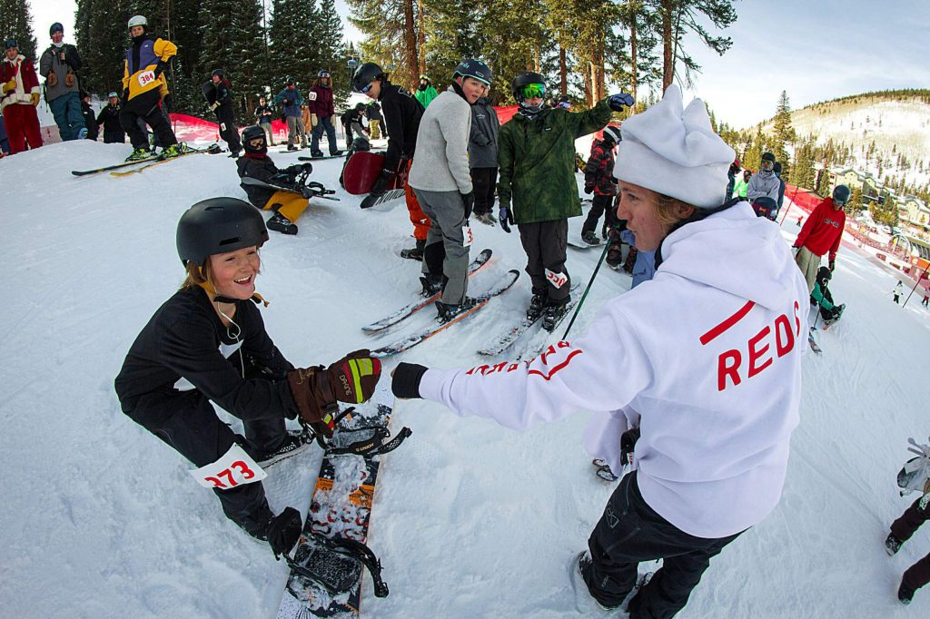 2018 Pyeongchang Olympic gold medalist and 2019 Burton U.S. Open champ Red Gerard, right, fist bumps a young snowboarder during Monday's grand-opening Red's Backyard rail jam at Copper Mountain Resort.