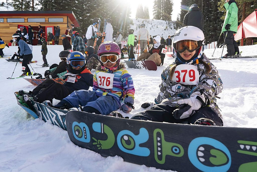 Young snowboarders take a break from hiking during Monday's grand-opening Red's Backyard rail jam competition at Copper Mountain Resort.