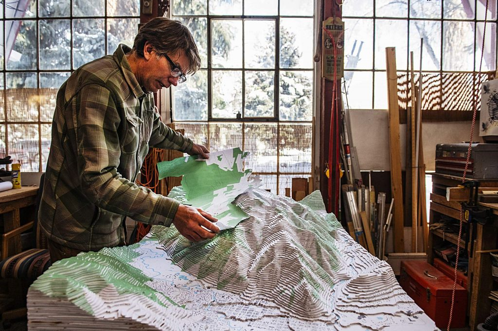John Doyle lays a map on top of his fully constructed map of Aspen and Aspen Mountain. Doyle used a large map and cut out individual sections to glue them onto the proper area of the three dimensional display.