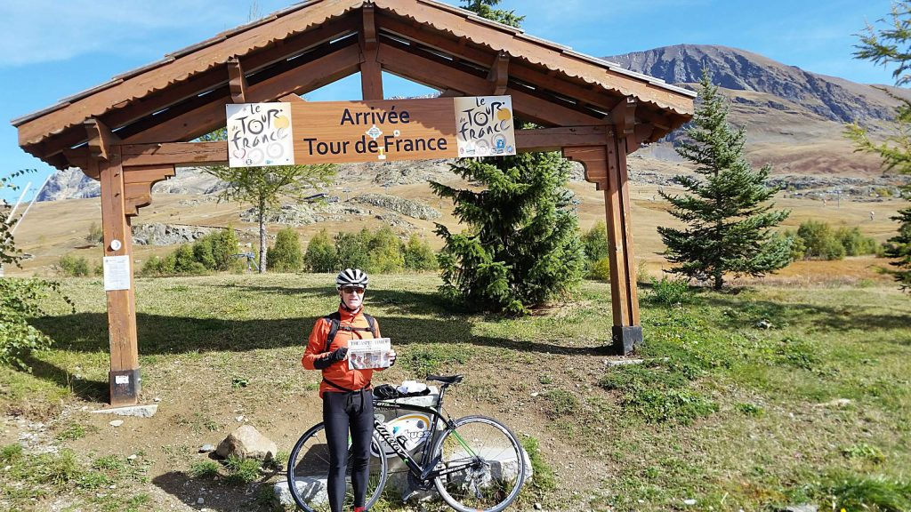 Roger Carlsen caught his breath to display The Aspen Times at the finish line of the Alpe D'Huez climb in the French Alps in October.