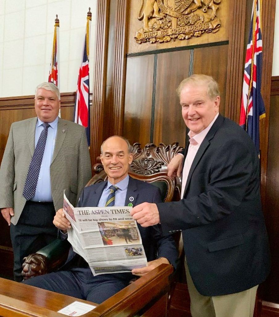 The Honorable Guy Barnett (sitting), a member of the Tasmanian House of Assembly, enjoys The Aspen Times in Parliament in Hobart, Tasmania, Australia. Standing on the right is Mac Cunningham of Basalt.