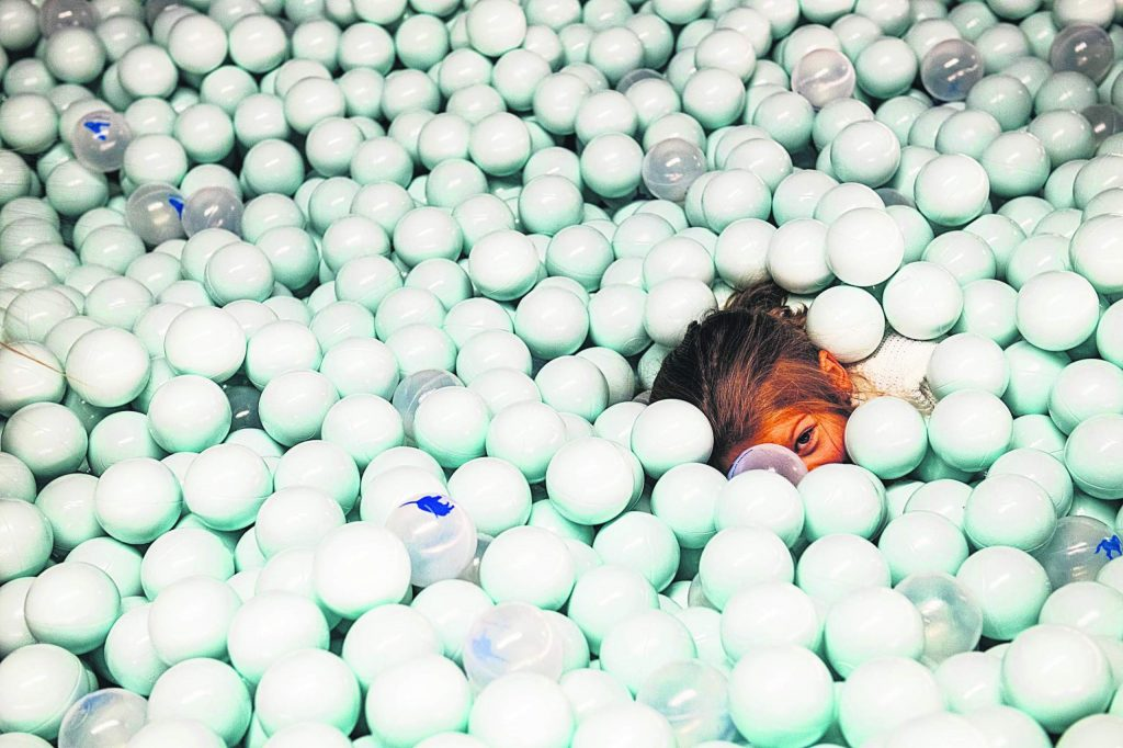Anja Malakhova, 4, peeks out from the ball pool during the grand opening of The Collective and MixSix in Snowmass on Saturday, December 7, 2019. (Kelsey Brunner/Snowmass Sun)