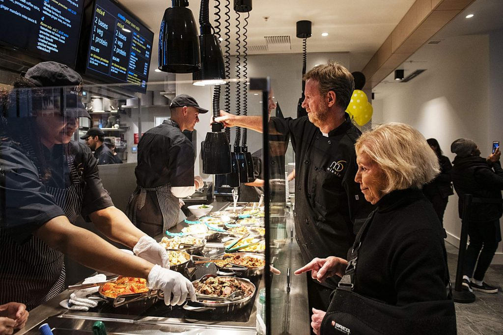 Snowmass Mayor Markey Butler, right, gets her food first during the grand opening of The Collective and MixSix with assistance from Chef Martin Oswald, center right, in Snowmass on Saturday, December 7, 2019. (Kelsey Brunner/Snowmass Sun)
