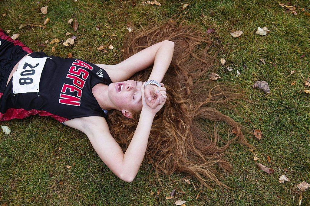 Aspen High School's Edie Sherlock lays on the ground catching her breath  after she competed in the 2019 Class 3A regional cross country meet in October at Crown Mountain Park in El Jebel.