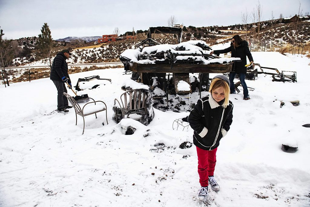 Jake Zamansky, left, and his wife Tara Dakides clean up the area around their burnt fifth-wheel RV as their daughter Meadow Anne Franklin Dakides Zamansky walks out of the snow on their property in Carbondale on Dec. 15, 2019. The children expressed that they loved living in the RV. Tara said that it was nice to feel like they had a home to feel settled in.