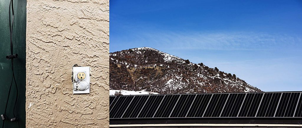An electrical outlet on the outside of a restaurant in the Snowmass Village Mall is pictured next to the newly installed solar panels that run the length of the roof of the Snowmass Village Recreation Center.