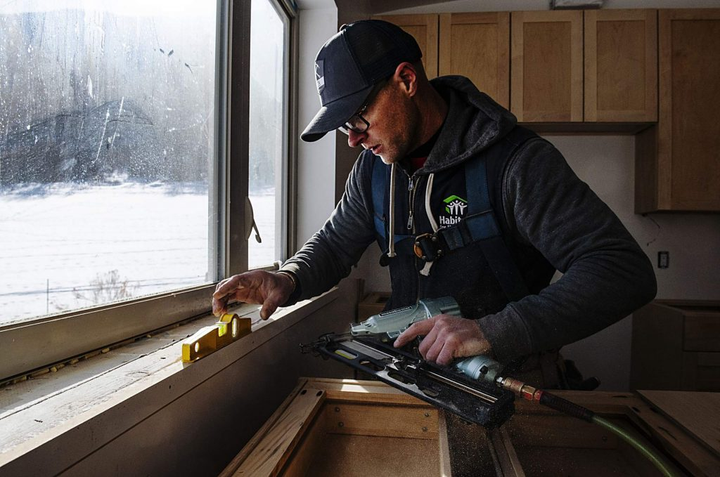 Habitat for Humanity carpenter Jordan Mathre installs aprons on the newly built windowsills in a home in the Basalt Vista project.