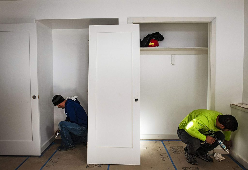 Jeremy Duncan, left, and Felipe Gomez caulk the trim in a home being built for the Habitat for Humanity Basalt Vista project. Duncan is a Basalt Vista homeowner and has a planned move-in date of 2021.