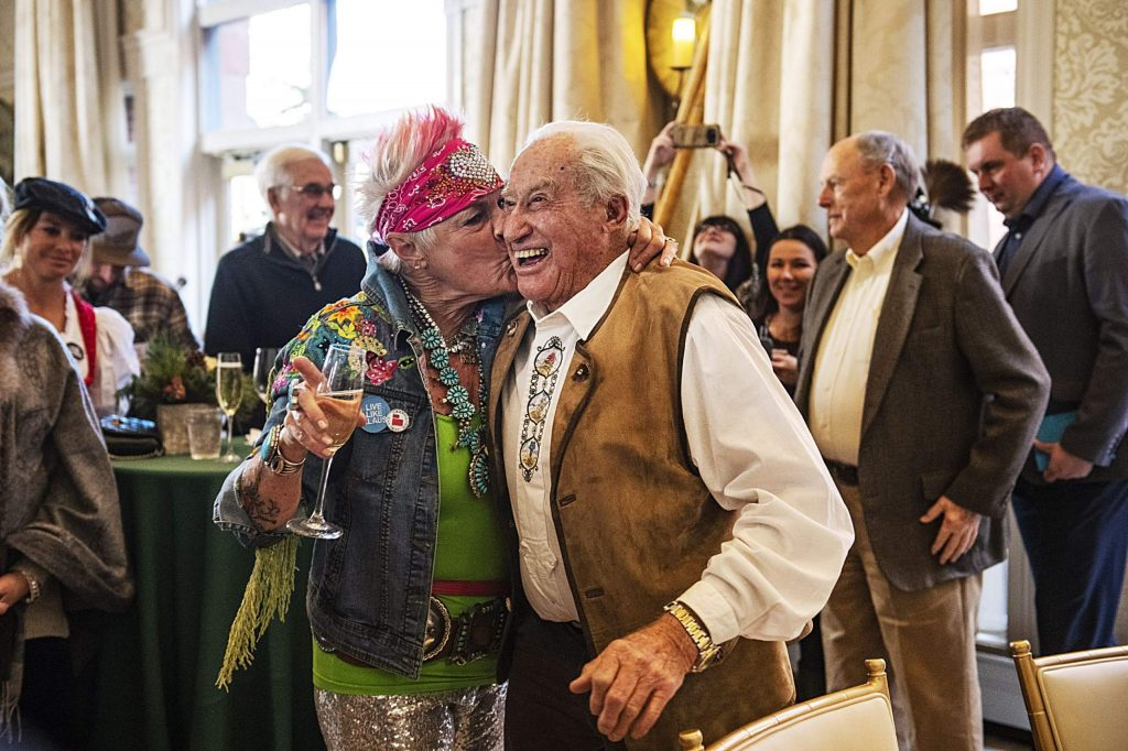 Amy Skaling, left, kisses the cheek of Klaus Obermeyer as he walks into his 100th birthday party at the Hotel Jerome on Monday. Skaling was a representative for Obermeyer for 29 years.
