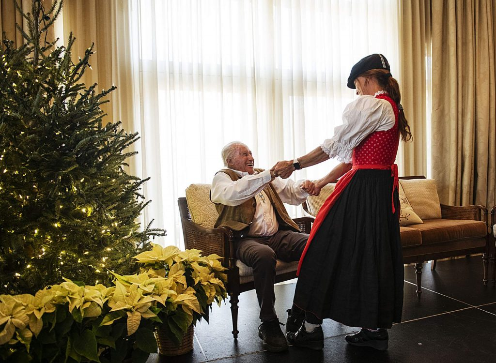 Kate McBride holds the hands of Klaus Obermeyer while wishing him a happy birthday during his party in the Hotel Jerome on Monday.