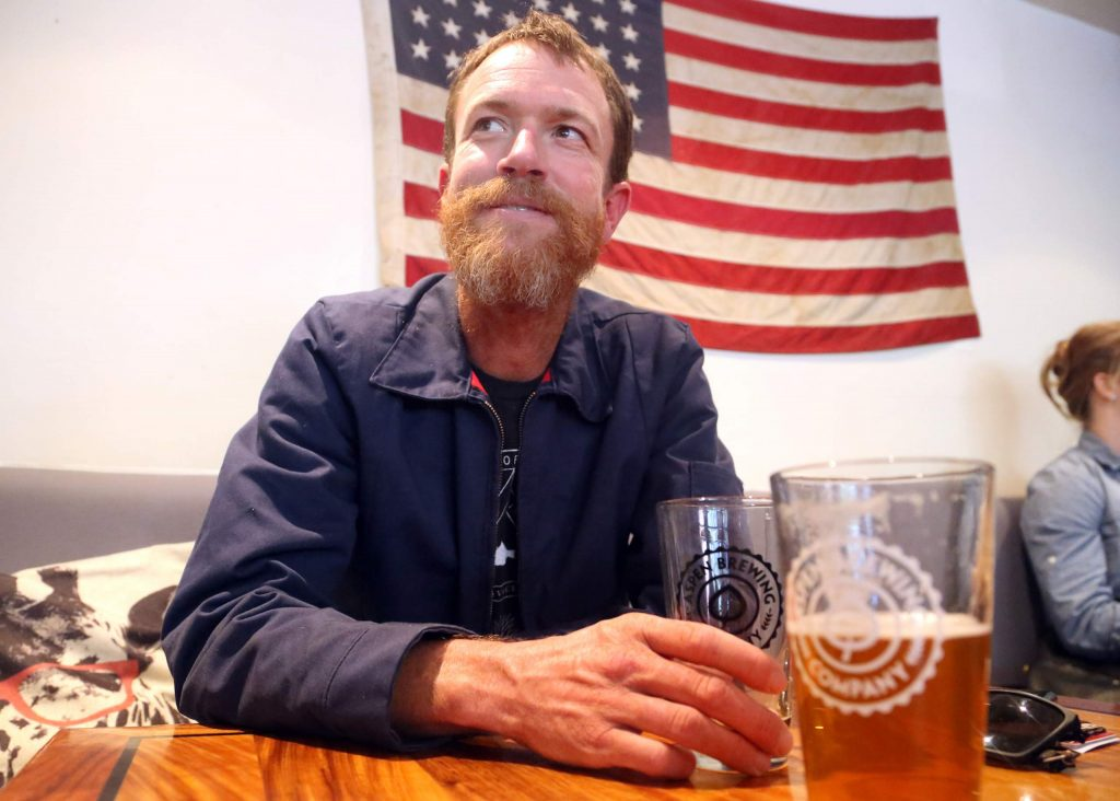 Rickey Gates enjoys a beer at Aspen Brewing Company in 2017 while visiting his hometown. Gates, an accomplished runner, was roughly two-thirds of the way through his Transamericana project at the time, which was to run from South Carolina to California, exploring the country along the way. He wrote a book about the experience that will go on sale this spring. (Photo by Austin Colbert/The Aspen Times)