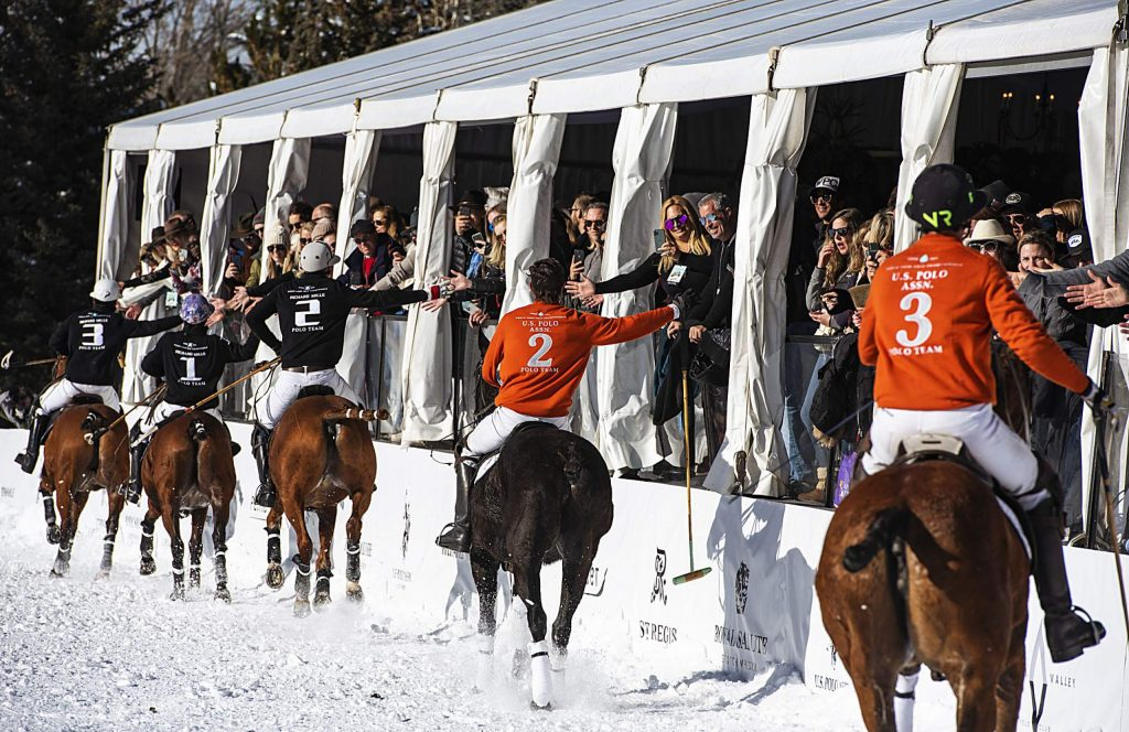 U.S. Polo Assn., in orange, and Richard Mille clap hands with those in the VIP tent after the final game at Rio Grande Park during the St. Regis World Snow Polo Championships in Aspen on Friday, Dec. 20, 2019. (Kelsey Brunner/The Aspen Times)