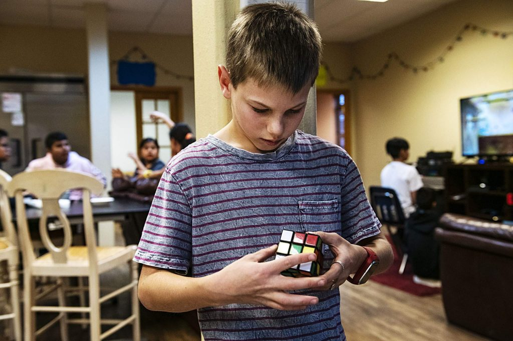 Anderson Bohmfalk, 12, solves a Rubic's cube puzzle in the middle school Stepping Stones building on Wednesday, December 11, 2019.
