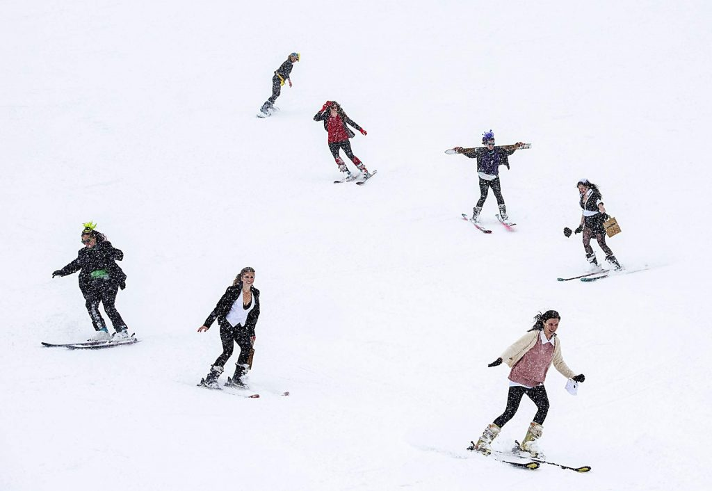 The Snowmass Tourism team skis down Little Nell during the Gay Ski Week downhill costume contest on Friday, Jan. 17, 2020. (Kelsey Brunner/The Aspen Times)