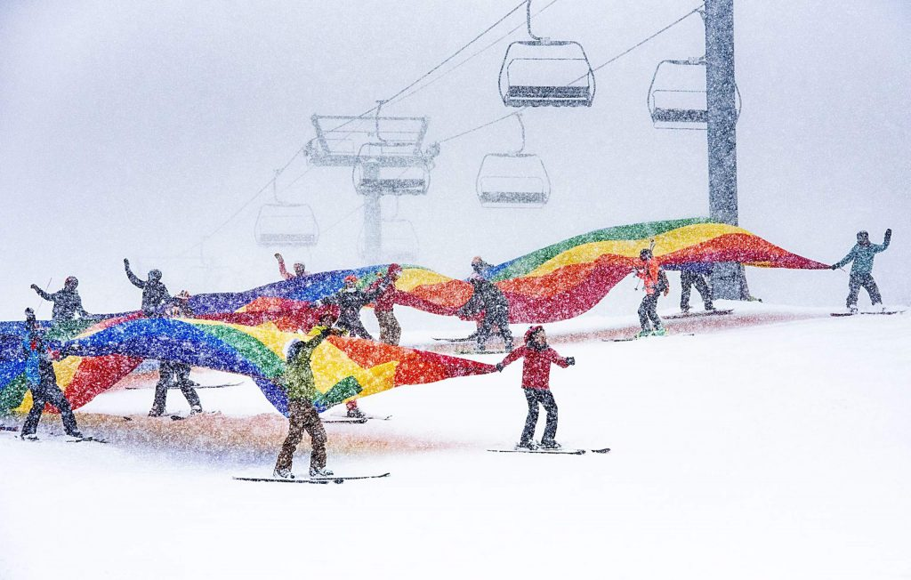 People ski down the Little Nell run on Aspen Mountain with a giant pride flag to end the downhill costume contest and party during Gay Ski Week on Friday, Jan. 17, 2020. (Kelsey Brunner/The Aspen Times)