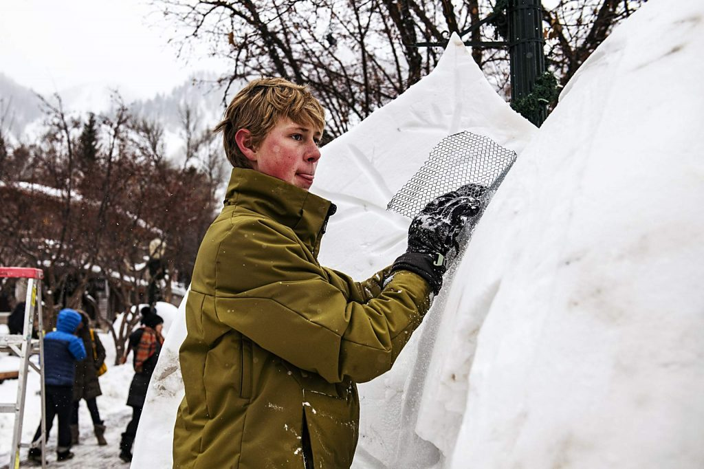 """Lars Earl shaves the snow on the finished Anderson Ranch Arts Center Wintersculpt piece titled """"Need for Green"""" on Saturday, January 11, 2020. The team that built the piece was comprised of all 8th grade students. """"We're just a bunch of friends that skipped school yesterday to make this,"""" said Earl. """"We drew our blueprint of what we wanted to do during recess."""" (Kelsey Brunner/The Aspen Times)"""