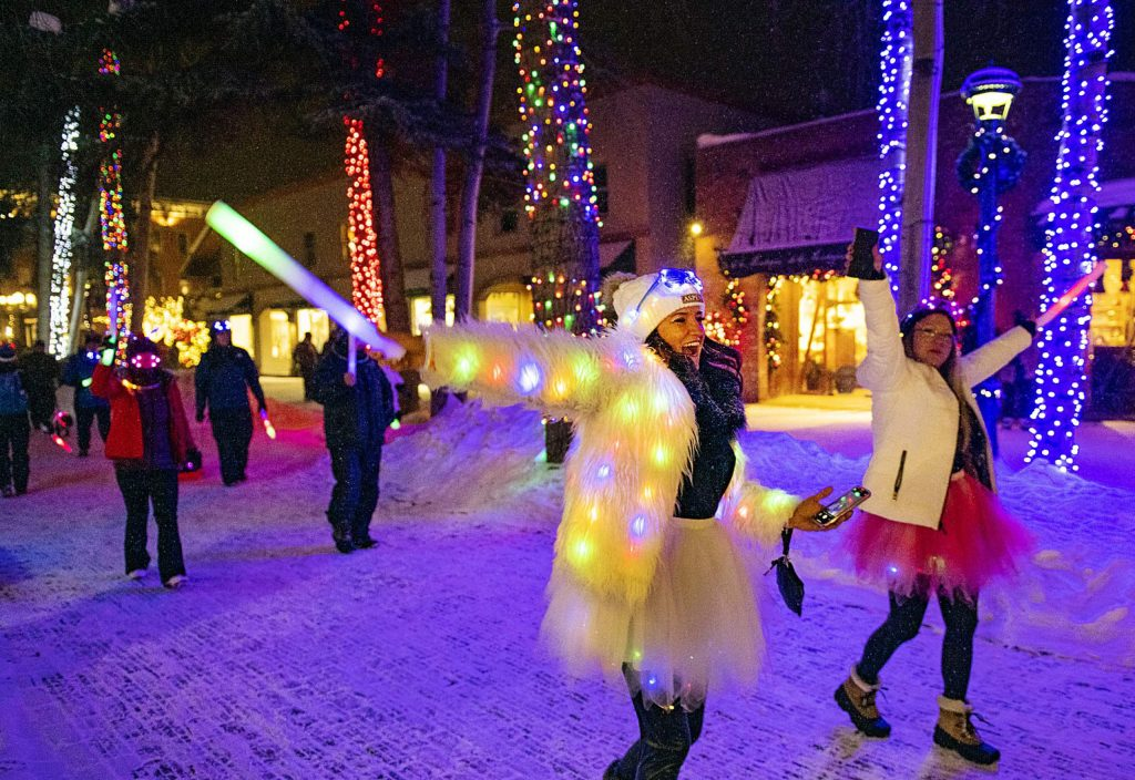 Michele Strobl, left, dances down Cooper Avenue during the Winterskol Aspen Glow Parade to the music played by the United States Air Force Academy Band on Saturday, January 11, 2020. (Kelsey Brunner/The Aspen Times)