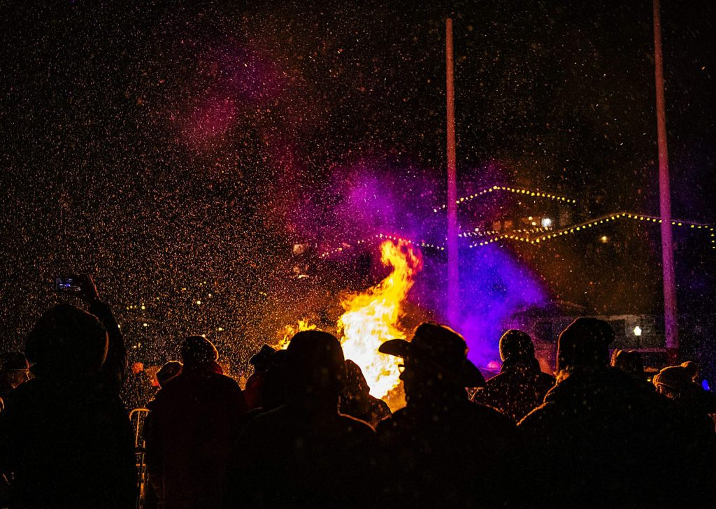 People warm themselves by the Winterskol Bonfire arrayed by the Aspen Chamber Resort Association and Aspen Fire Department on Saturday, January 11, 2020. The 3rd annual Snowcoming Winterskol Bonfire also offered free chili, cookies and hot chocolate, as well as music to enjoy.(Kelsey Brunner/The Aspen Times)