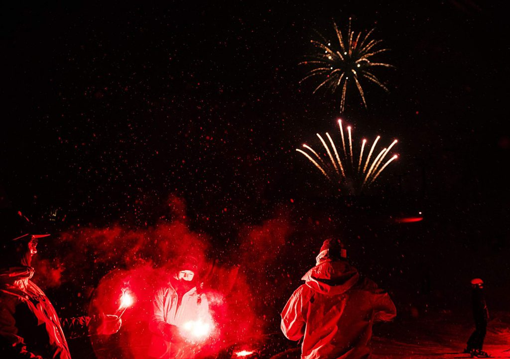 People watch the Fireworks Extravaganza after reaching the base of Aspen Mountain from participating in the Torchlight Descent during the 69th annual Winterskol on Saturday, January 11, 2020. (Kelsey Brunner/The Aspen Times)
