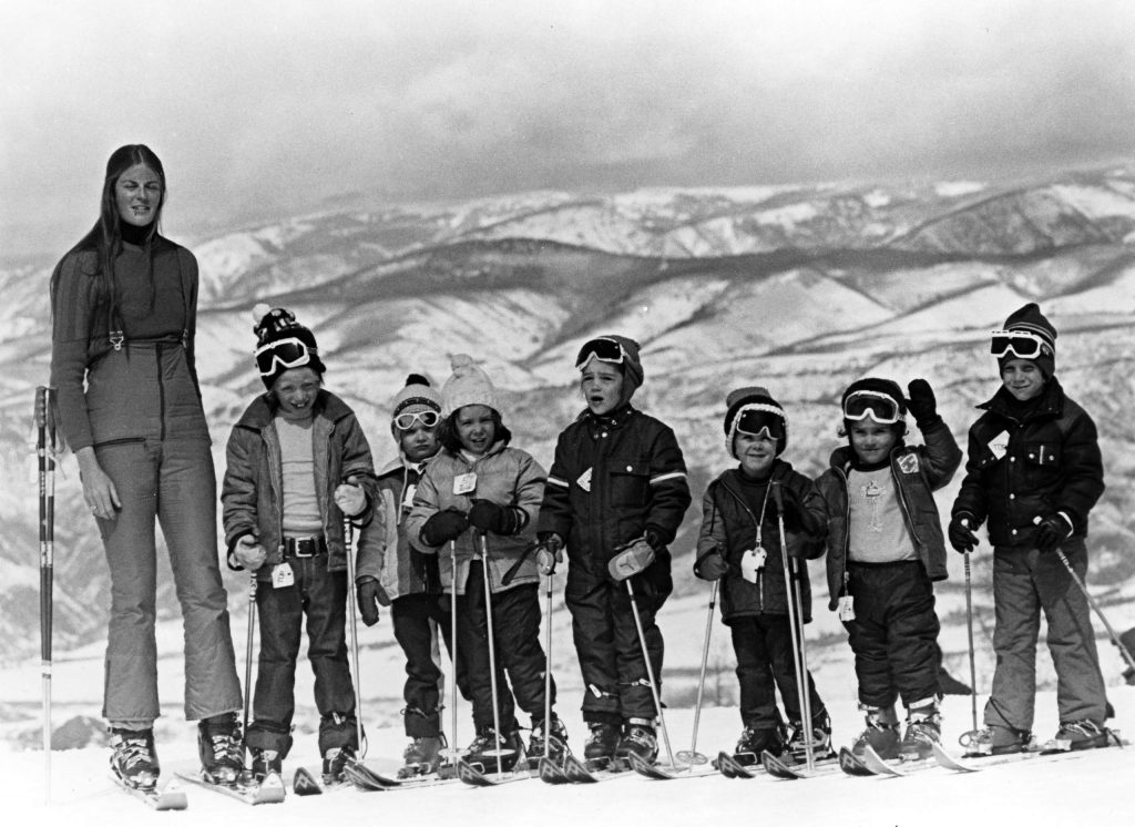 An instructor and a children's ski school class.