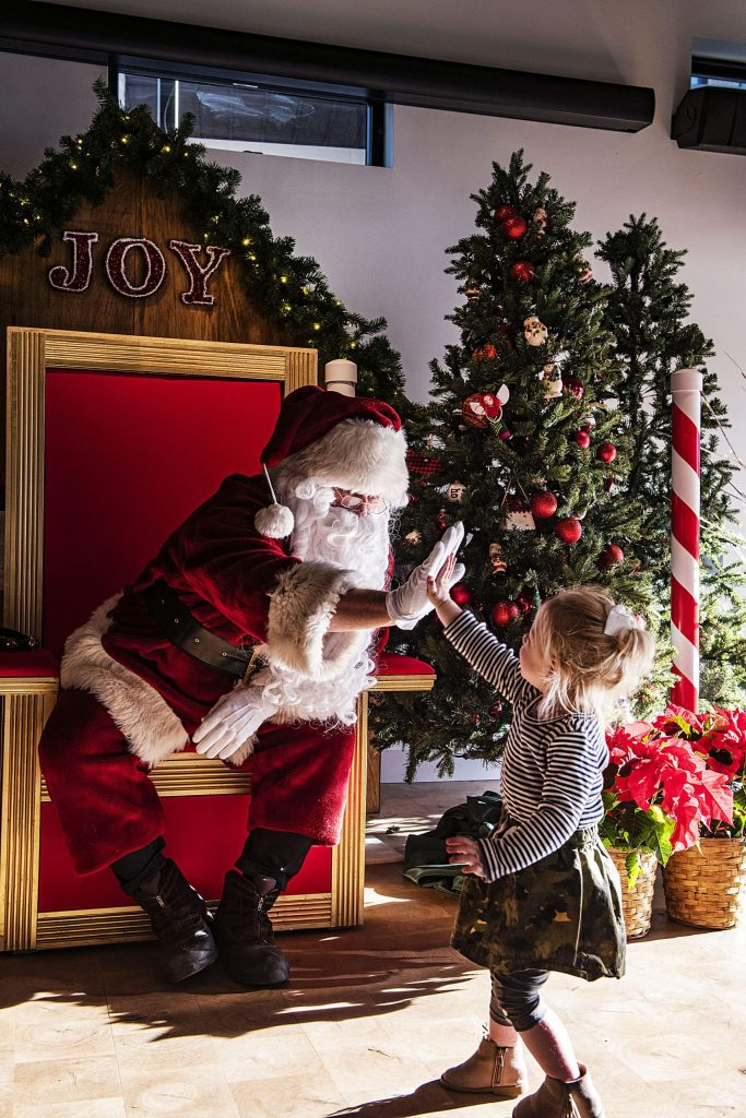 Bill Boineau, dressed as Santa, gives a high-five to August Smith, 2, in Santa's Village in The Collective in the Snowmass Base Village on Saturday, December 21, 2019.