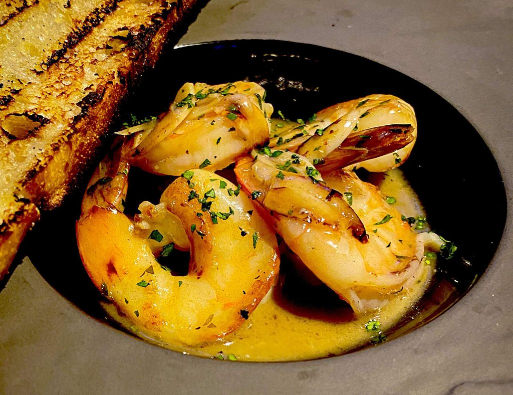 Pan-seared shrimp in a roasted garlic-Chenin blanc sauce with grilled sourdough bread.