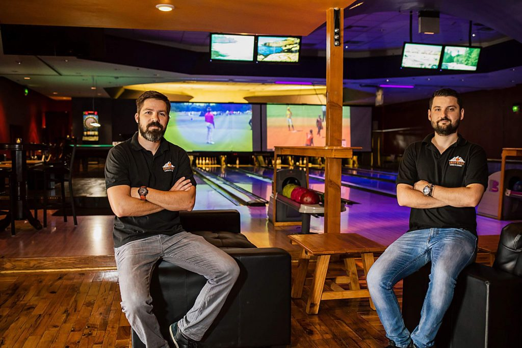 From left, owners Borko Orlic and Marko Pavlovic sit in Snowmass Lanes and Lounge, located on the Village Mall.