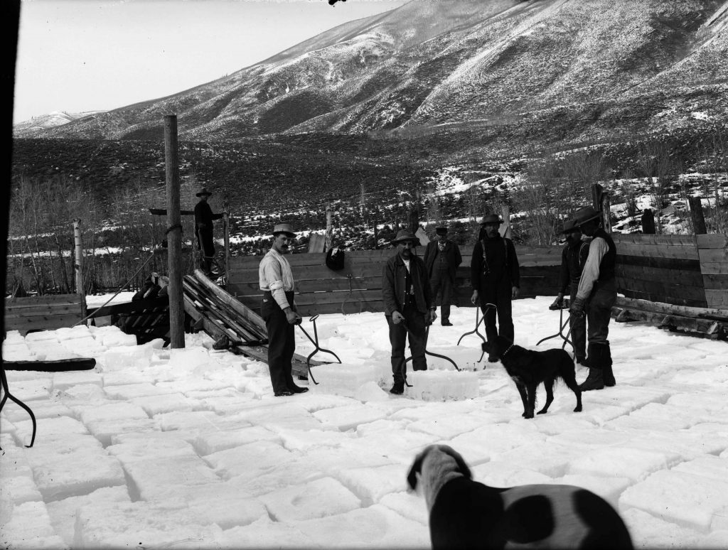 Men use tongs to move ice blocks at an ice operation in Aspen in a photo likely taken between 1893 and 1895. Red Mountain is in the background. The man in the center background is Edmund C. Hawkins, who also worked in Ashcroft.
