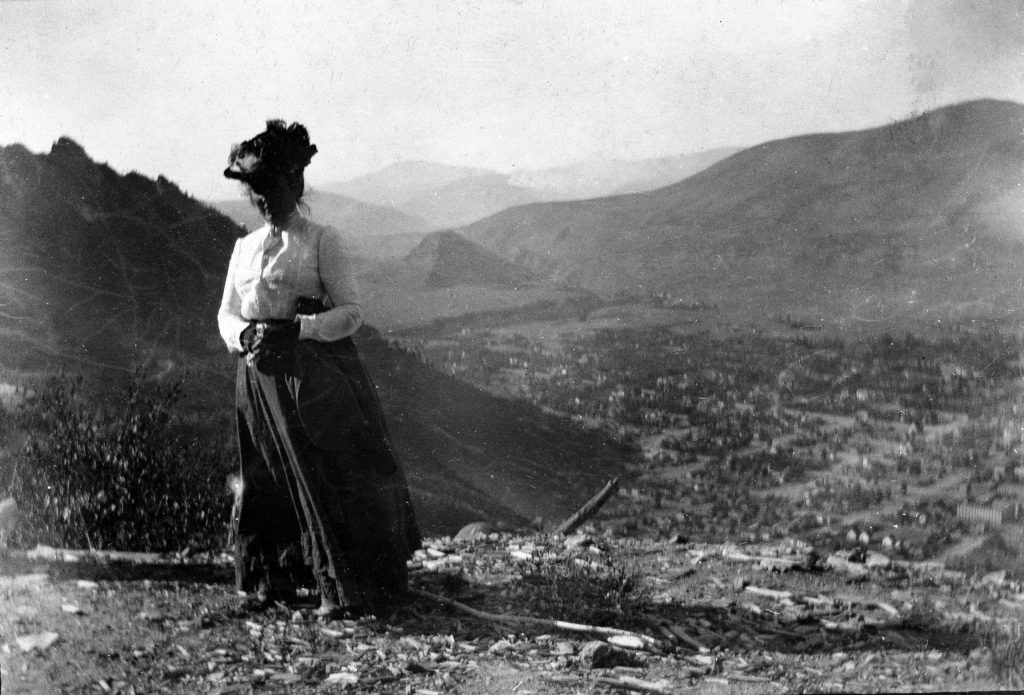 A woman identified as Nellie Bird stands on Little Nell in the late 1880s. Aspen and Red Mountain can be seen in the background. Bird moved from Leadville and had interests in Aspen and Ashcroft.