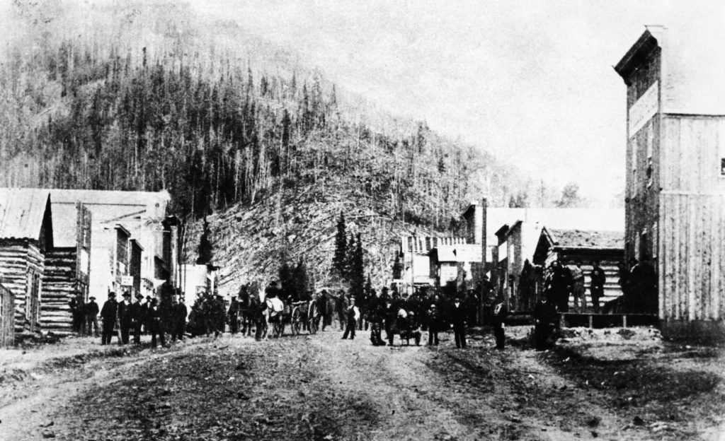 A crowd gathers in a street at Ashcroft on July 4th, 1882. The town was bustling at that time because of local mining activity.