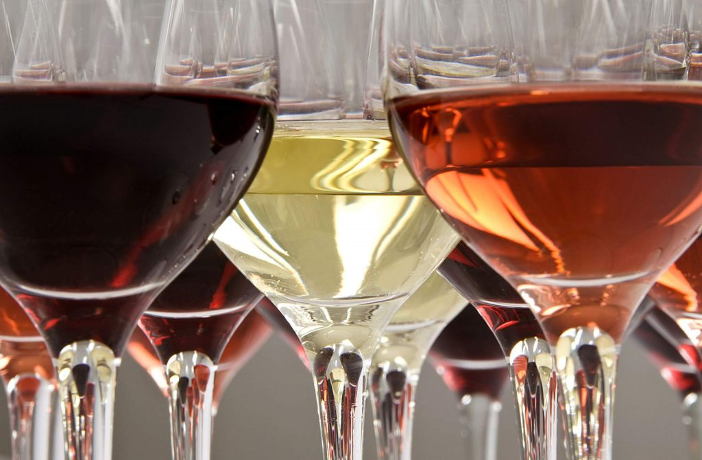 Red, rosé and white wine in crystal glasses.