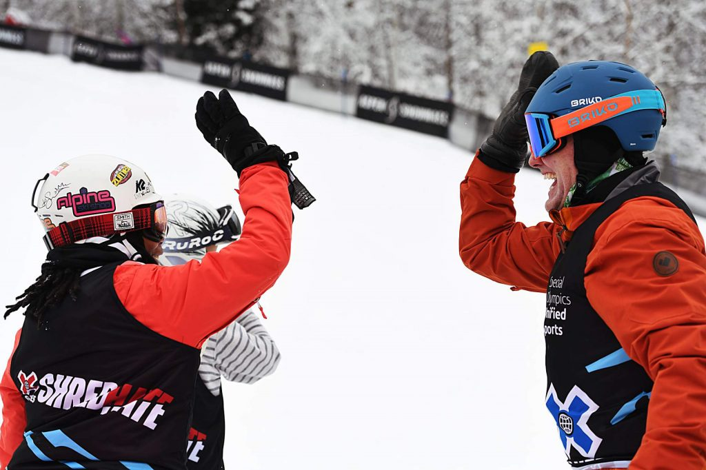 Chris Klug high-fives teammate Latrice Pringle after finishing his heat during the X Games Unified Special Olympic snowboard event on Thursday, Jan. 23, 2020. (Kelsey Brunner/The Aspen Times)