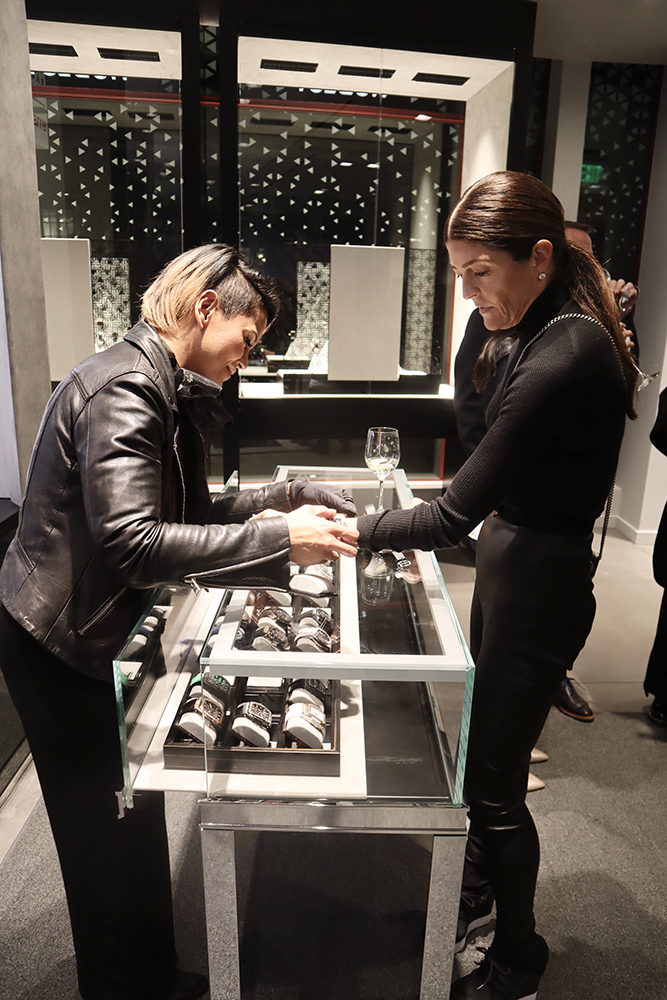 Fashion designer Ruthie Davis tries on a women's watch at the Hublot Aspen boutique opening.