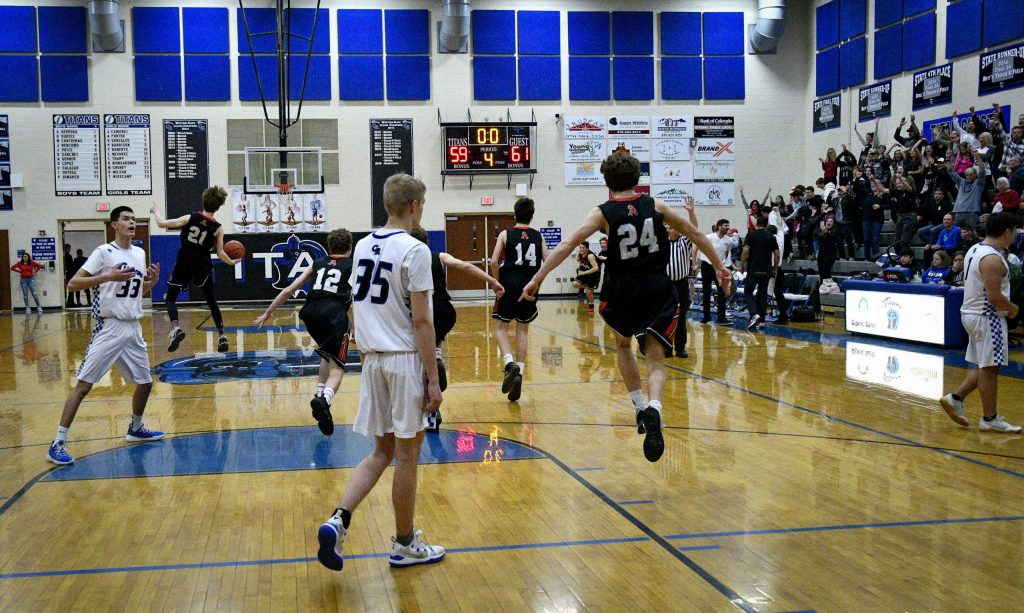 Coal Ridge's Irvin Ortega, Hank DiMarco and Andrew Herrera walk off the court stunned as Aspen celebrates a two-point victory in overtime on Tuesday in New Castle.