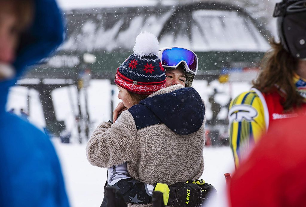 Evelyn Leibinger, left, hugs teammate Jake Morgan after he fell during his first run of the Aspen High School Giant Slalom State Qualifier at Aspen Highlands on Thursday, Feb. 6, 2020. (Kelsey Brunner/The Aspen Times)
