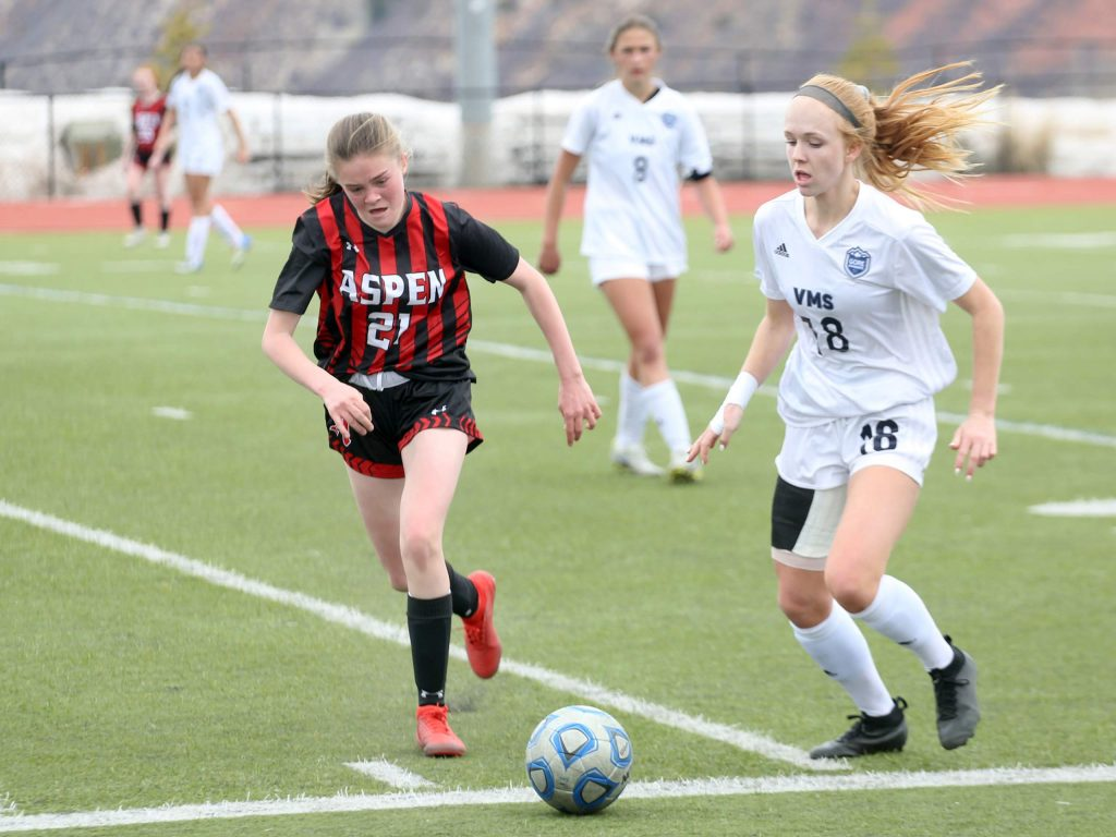 Jenny Ellis, left, attacks as the Aspen High School girls soccer team plays against Vail Mountain on Saturday, April 6, 2019, on the AHS turf. Ellis' father, Chris Ellis, will take over as the team's head coach for the 2020 spring season. (Photo by Austin Colbert/The Aspen Times).