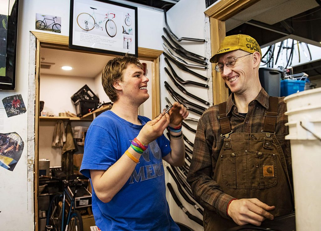 Dylan, left, and Aaron Taylor share a joke while working in the Way of Compassion bicycle project shop in Carbondale on Thursday, Feb. 13, 2020. Taylor is the director of the bicycle project and was assisting Dylan in a project.