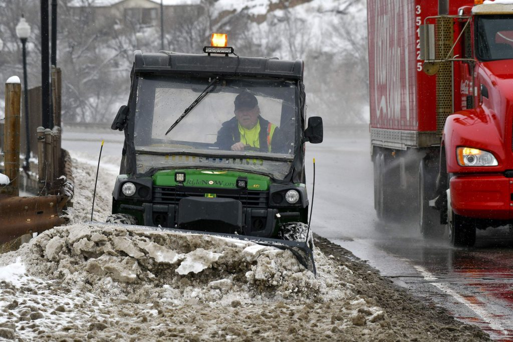 A city of Rifle employee plows off the sidewalks near I-70 in Rifle Friday. Crews were busy cleaning up the snow left by the snow storm that swept through the area Thursday and early Friday.