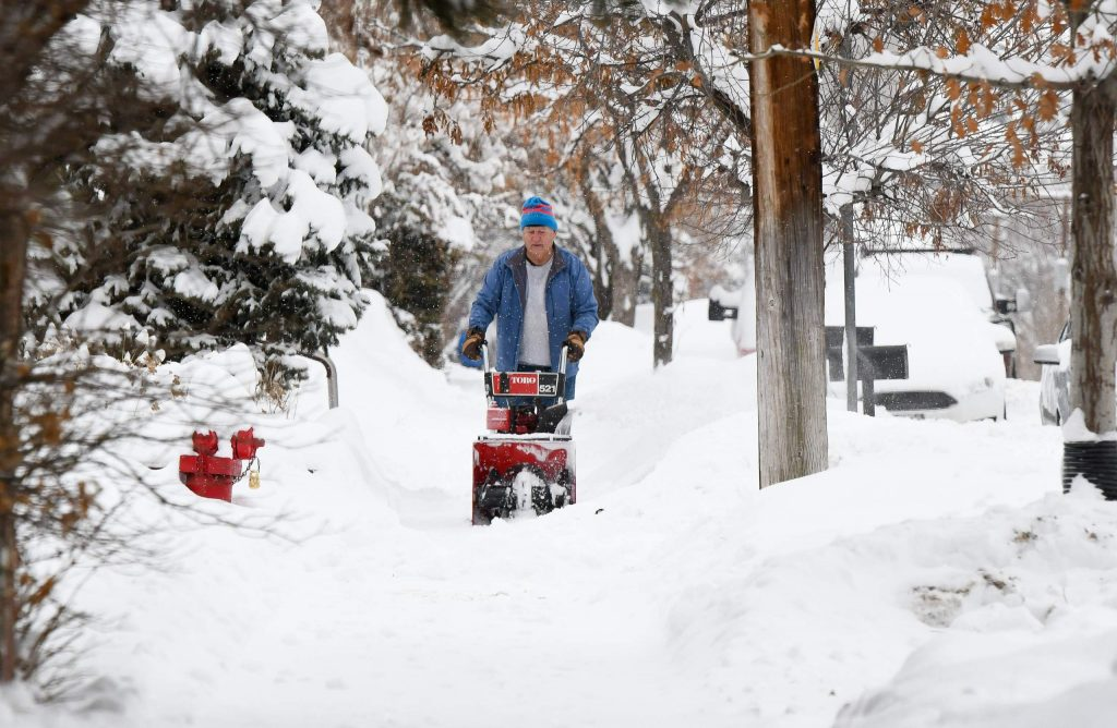 A man runs a snowblower down the sidewalk in downtown New Castle on Friday morning after a heavy snowstorm left close to a foot of snow in the area.